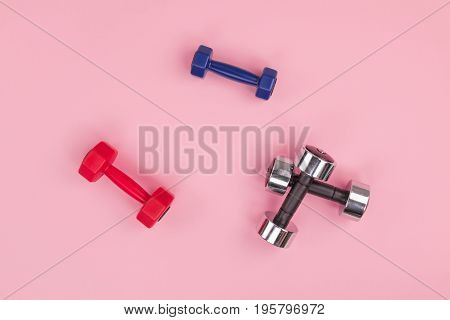 Top View Of Set Of Various Dumbbells Isolated On Pink