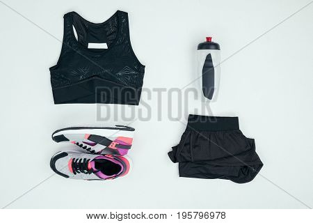 Top View Of Sportswear With Sneakers And Sports Bottle Isolated On Grey