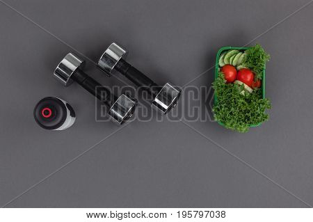 Top View Of Dumbbells With Sports Bottle And Vegetable Salad Isolated On Grey