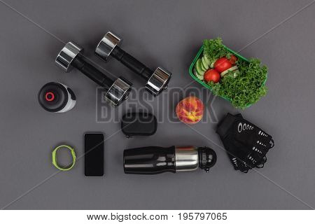 Top View Of Smartphone With Fitness Tracker, Dumbbells And Vegetable Salad Isolated On Grey
