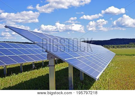 Solar panels on field. Beautiful cloudy sky on background.
