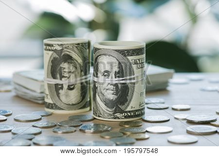 Selective Focus Of Dollar Banknotes In Rolls With Rubber Bands And Coins On Table