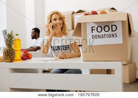 We are ready to send. Confident motivated persistent lady making a phone call and confirming something while preparing packages with humanitarian aid