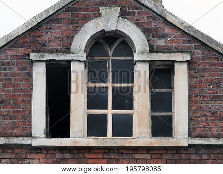 broken windows in an abandoned derelict old commercial building with brickwork stone frame and roof Halifax england