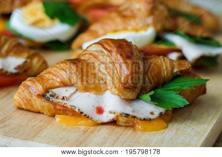 Butter croissant with chicken ham cheese and parsley on wooden board. Hot breakfast sandwich. Healthy appetizer