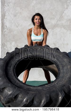 Beautiful young woman in bright sexy shorts with pretty athlete muscular body lift up big heavy tire with happy smile. Cross training urban area street gym city exercise routine healthy lifestyle.