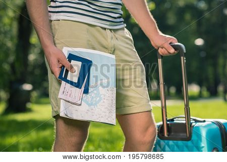 Cropped shot of young tourist with suitcase holding map passports tickets and credit card in park