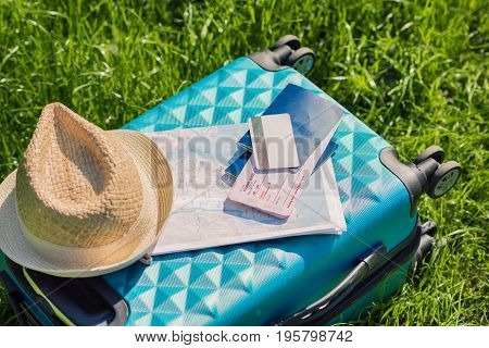 passports tickets map credit card and straw hat lying on blue suitcase