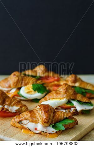 Vertical photo of hot sandwiches with mini croissants chicken ham cheese parsley tomato and eggs served on wooden board blackboard as background