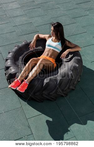 Beautiful young lady with long legs in bright sexy shorts with pretty athlete muscular body rest in big heavy tire. Cross training urban area street gym city exercise routine healthy lifestyle.
