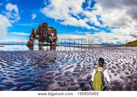 The Basalt rock - Mammoth Hvitsercur during an ocean outflow. Woman with a green backpack admiring the natural wonder. Concept of extreme northern tourism in Iceland