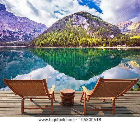 Pair of comfortable sun loungers on the lake. Magnificent lake in South Tyrol, Italy. The concept of walking and eco-tourism. Water reflects the surrounding mountains and forest