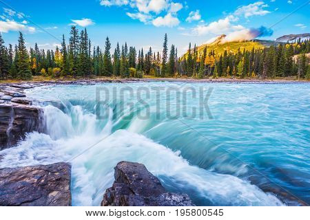 The full-water bubbling waterfall of Athabasca. The concept of extreme and ecological tourism. Clear autumn evening in Canada