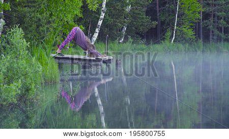 Young woman doing yoga exercises on the lake shore. Artha mukha svanasana