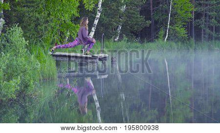 Young woman doing yoga exercises on the lake shore. Virasana
