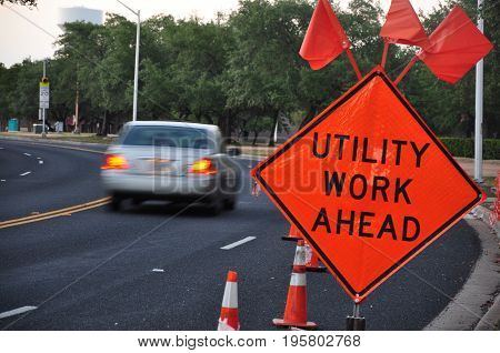 A utility work sign and traffic cones on a road with a car and trees in the background