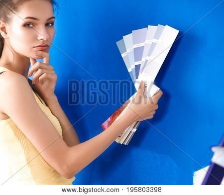 Young beautiful woman holding color palette , standing near wall.