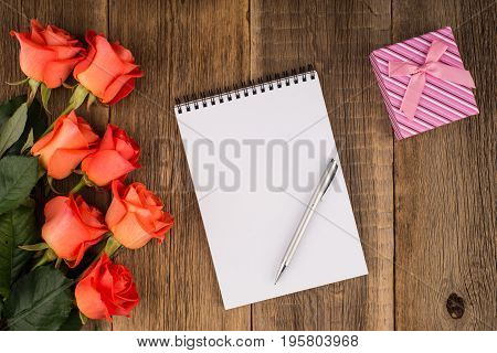 Blank notebook pen with a rose and a gift on a wooden table. Top view.