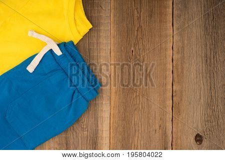 Sport children's clothes on the old wooden table. Top view.