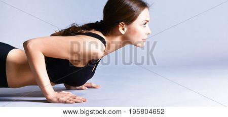 Portrait of young woman doing push ups