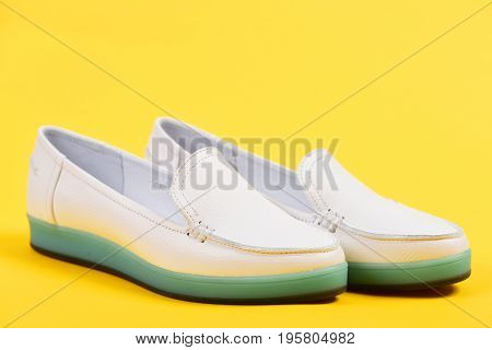 Summer fashion and casual lifestyle concept. Low heel footwear in sports style. Pair of female leather shoes isolated on light yellow background selective focus. Moccasins for women in white color