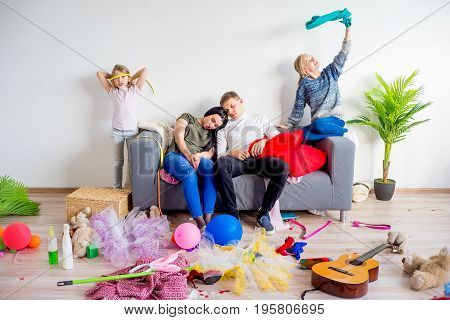 Parents are sleeping while the children have arranged a mess near them