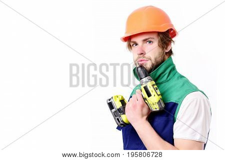 Construction worker holds yellow drilling tool near chin. Man with serious face expression isolated on white background. Builder in orange helmet and uniform. Work in progress and repairing concept
