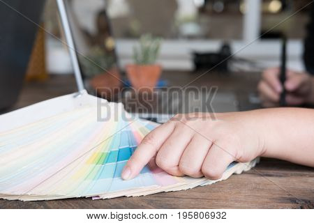 Graphic Or Interior Designer Choosing A Colour From Color Swatch Sampler Or Catalogue Palette Guide