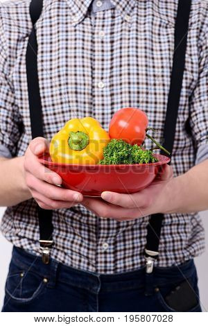 Man holds red bowl of bell pepper parsley and tomato. Healthy lifestyle and diet concept. Idea of proper nutrition. Farmer with fresh vegetables on plaid shirt background defocused