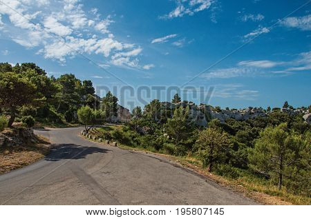 Road crossing forest and rock formations with blue and sunny sky, near the village of Baux-de-Provence. Bouches-du-Rhône department, Provence-Alpes-Côte d'Azur region, in southeastern France