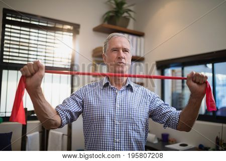 Senior man pulling fabric while standing in hospital ward