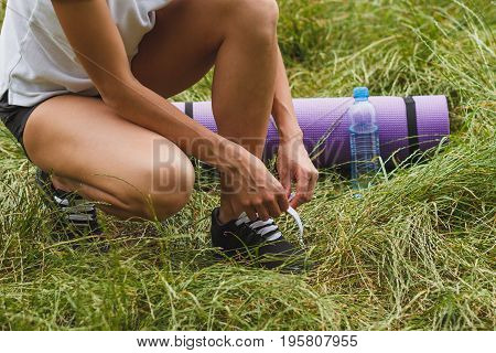 Sporty Woman On The Green Grass With A Mat And Bottle With Water