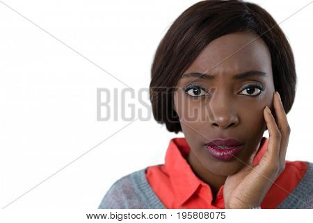 Portrait of surprised young woman with hand on chin against white background