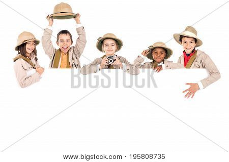 Children's group with safari clothes and gear over a white board