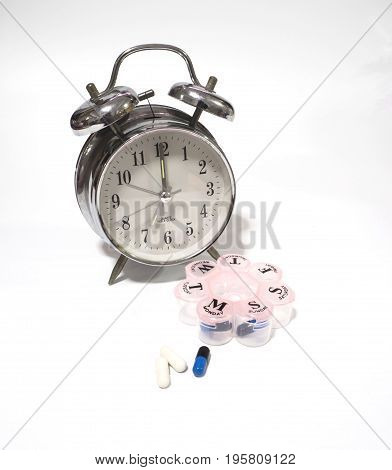 Capsule and pill box with alarm clock medicine time concept