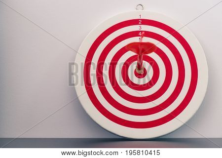Red bullseye dart with red arrow hit center of dartboard - business concept of success and goal achievement - vintage tone