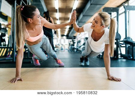 Two attractive fitness girls doing push ups in gym