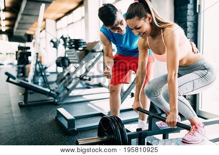 Atrractive woman doing exercises for back with personal trainer in gym