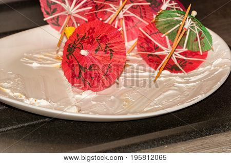 Empty white dessert plate plate on a kitchen plate with remains of cake decoration material.