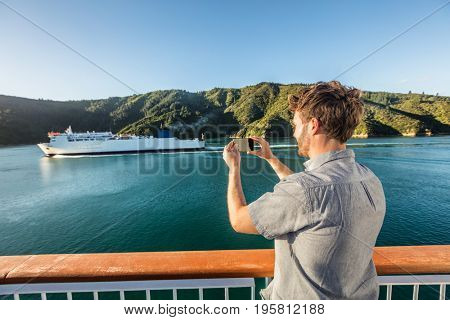 Cruise travel man tourist taking phone picture of ferry boat cruising on sea. Tourism photos during New Zealand island crossing holiday at Marlborough sounds Cook strait.
