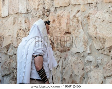 Jerusalem Israel July 14 2017 : Religious Jewish young man reads prayers outside the fortress walls of the old city of Jerusalem Israel