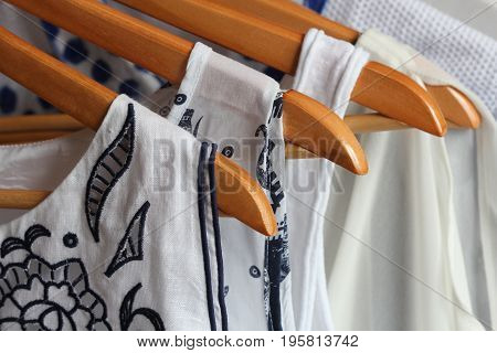 Summer collection of women's clothes hanging on a rack .