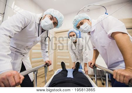 Sick patient on gurney in operating room with doctors in front of him