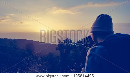 Male backpacker taking photograph at sunset in morning. Travel to Doi Inthanon Chiangmai Thailand.