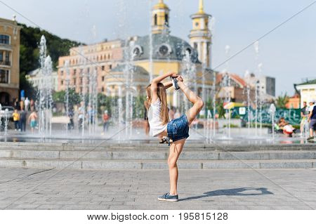 Active kid girl gymnast stretching on the street. Young girl acrobat. The girl is engaged in gymnastics