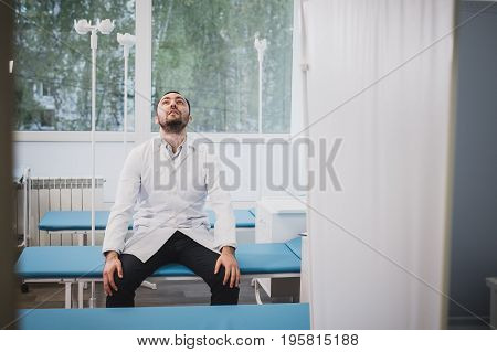 Tired doctor sitting alone in hospital ward