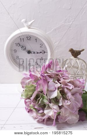 Postcard with pink hydrangea flowers and clock on light textured background. Shabby chic. Vertical image.