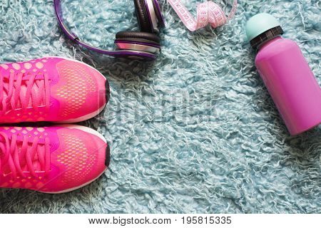 Pair of pink sport shoes meter water bottle and headphone over fur carpet. In the fitness room background. Accessories for running sport and exercise.
