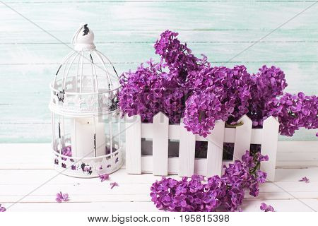 Fresh lilac flowers in box and candleholder with candle in form of cage on white wooden background against turquoise wall. Selective focus. Shabby chik vintage decorations.