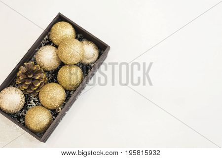 Golden Christmas Balls In A Wooden Crate On A White Rustic Wooden Background. Top View